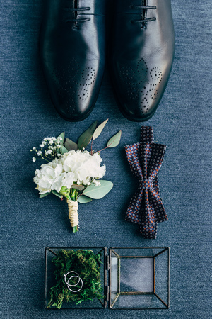 flat lay with arrangement of grooms shoes, bow tie, corsage and wedding rings for rustic wedding on blue background Stockfoto