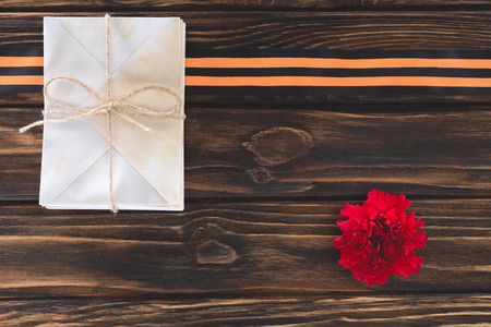 top view of box wrapped by string, carnation and st. george ribbon on wooden planks Stock Photo - 106575379