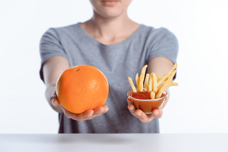 cropped shot of girl holding ripe orange and ketchup with french fries