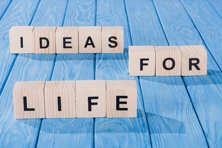close up view of arranged wooden blocks into ideas for life phrase on blue wooden surface