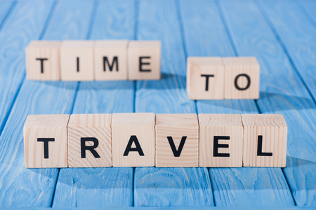 close up view of arranged wooden blocks into time to travel phrase on blue wooden surface