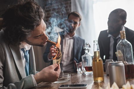 young businessman holding dollar banknote and smoking cigar while partying with friends