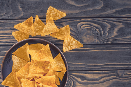top view of crispy unhealthy nachos in bowl on wooden table Stock Photo