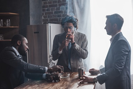 young multiethnic businessmen smoking cigars and drinking alcohol together