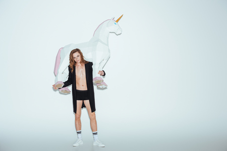 fashionable man in boxer shorts and black jacket holding big unicorn, on grey Archivio Fotografico - 106577426