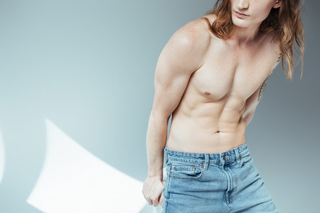 cropped view of young sexy shirtless man posing for fashion shoot, on grey Banque d'images - 106577488
