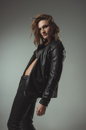 stylish man with long hair posing in black leather jacket, isolated on grey Фото со стока