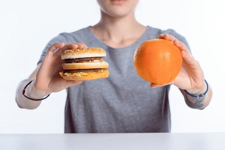 cropped shot of girl holding hamburger and ripe orange