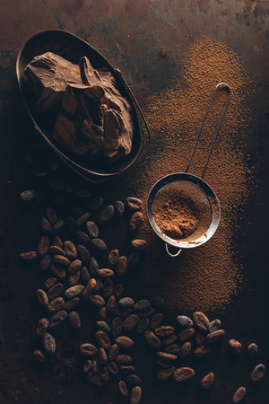 delicious chocolate pieces, cocoa beans, powder and sieve on dark surface Archivio Fotografico - 106577921