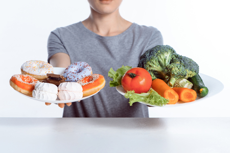 cropped shot of woman holding plates with sweets and vegetables