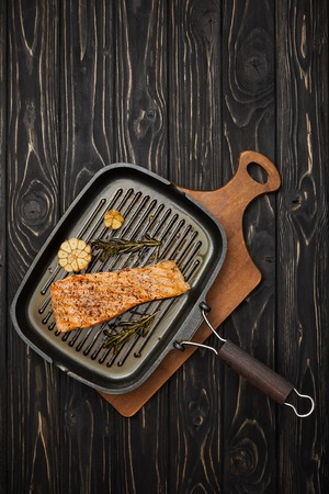 top view of arranged grilled salmon steak with rosemary on cutting board on black wooden tabletop