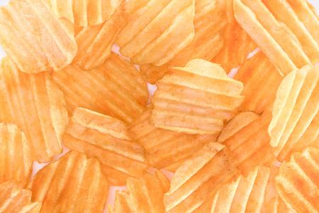 full frame view of crispy unhealthy potato chips background on white