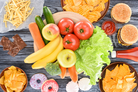 top view of assorted junk food and fresh fruits with vegetables on wooden table Stock Photo