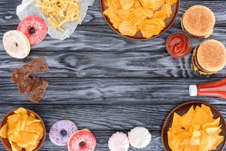 top view of assorted junk food and sweets on wooden table