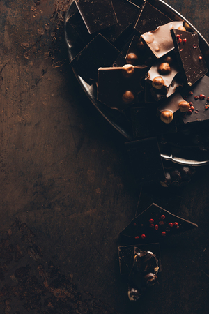 top view of arranged assorted delicious chocolate pieces with nuts on dark surface Stock Photo