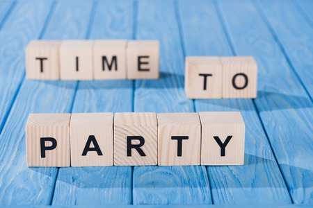 close up view of arranged wooden blocks into time to party phrase on blue wooden surface