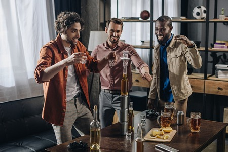 cheerful male multiethnic friends looking at tower from bottles and glasses while partying indoors