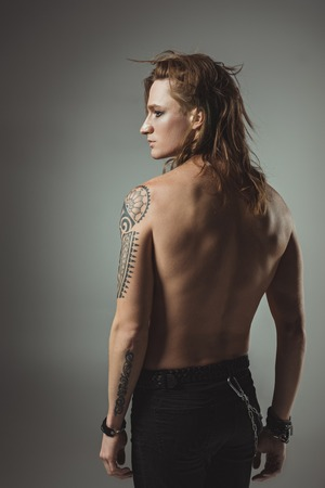 shirtless tattooed man with long hair posing in black jeans, isolated on grey Banque d'images - 106579155