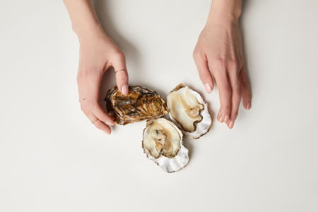 Female hands with fresh oysters on white table