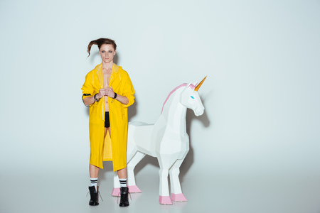 fashionable man with hairstyle in yellow raincoat standing with big unicorn toy, on grey Stockfoto