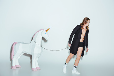 fashionable man in black jacket with big unicorn on chain, on grey Archivio Fotografico - 106579161