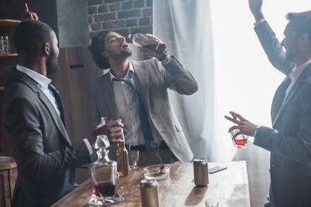 Felices amigos multiétnicos en trajes bebiendo alcohol y fumando puros juntos
