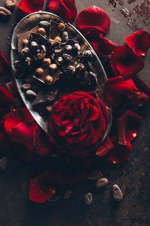 top view of beautiful red rose petals and gourmet chocolate with hazelnuts on dark surface