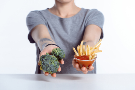 cropped shot of girl holding fresh broccoli and ketchup with french fries