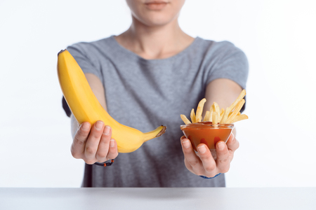cropped shot of girl holding ripe banana and ketchup with french fries