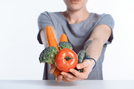 close-up view of woman holding fresh ripe vegetables