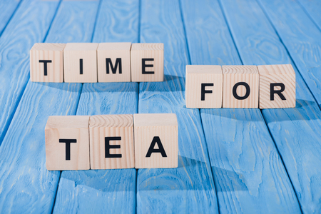 close up view of arranged wooden blocks into time for tea phrase on blue wooden surface Stockfoto