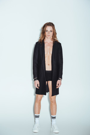 fashionable man with long hair posing in boxer shorts and black jacket, on grey