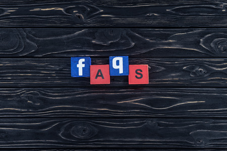 top view of word faqs made of wooden blocks on dark wooden tabletop