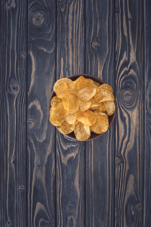 top view of crispy unhealthy potato chips in bowl on wooden table Stock Photo