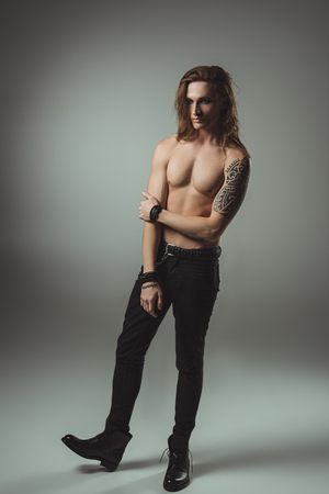 handsome shirtless man with tattoo posing in black jeans, on grey