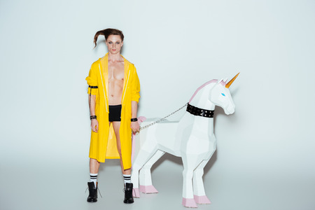 male model in boxer shorts and yellow raincoat standing with big unicorn toy on chain, on grey Stockfoto