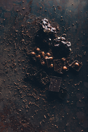 top view of delicious assorted chocolate pieces with nuts on dark surface Stock Photo