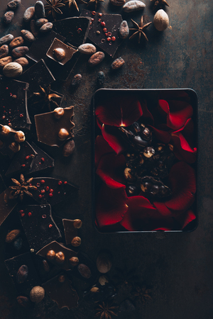 top view of red rose petals in box with delicious chocolate pieces, nuts and cocoa beans on dark surface Stock Photo