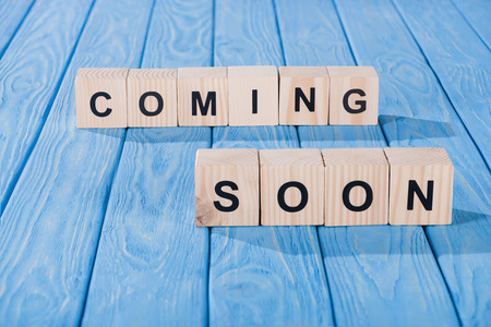 close up view of arranged wooden blocks into coming soon phrase on blue wooden surface Stock Photo