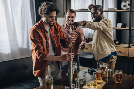 happy multiethnic male friends building tower from glasses and cans while partying together Stok Fotoğraf - 106584295