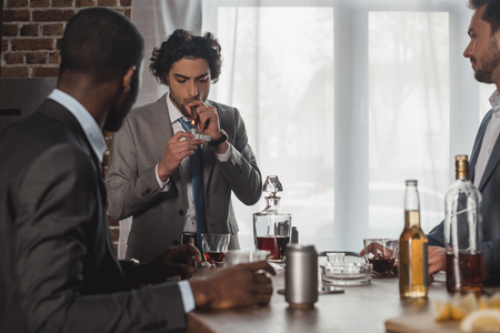 cropped shot of multiethnic men drinking alcohol and looking at friend smoking cigar