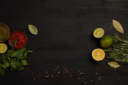 flat lay with sauce, citrus fruits pieces, spices, parsley and rosemary on black surface