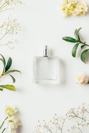 Vista superior de la botella de perfume rodeado de flores y ramas verdes sobre blanco