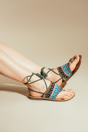 cropped shot of woman feet in stylish sandals on beige background Standard-Bild