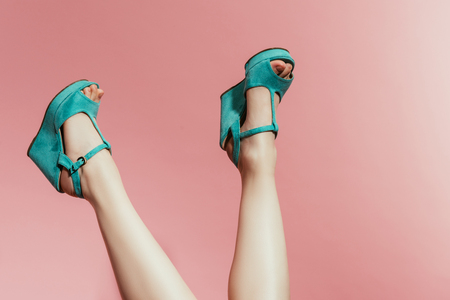 cropped image of upside down woman legs in stylish platform sandals isolated on pink background