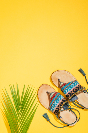 top view of palm leaf and stylish female sandals on yellow background