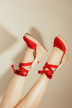 cropped image of upside down female feet in stylish red platform sandals on beige background Foto de archivo