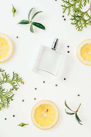 Vista superior de la botella de perfume con ramas verdes y rodajas de limón sobre blanco