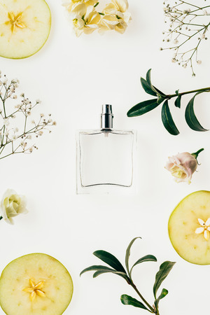 top view of bottle of perfume surrounded with flowers and apple slices on white Imagens