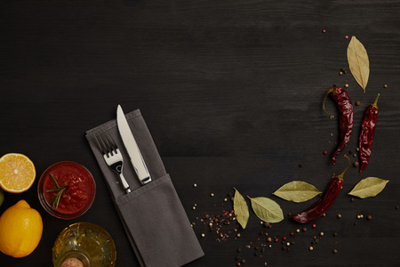 flat lay with cutlery, sauce, chili peppers, spices and lemon pieces on black tabletop